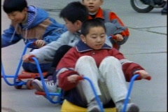 China, Xian, young boys in toy car, close-up Stock Footage