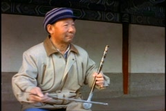 China, Beijing, man plays a single string instrument with a bow, medium shot Stock Footage