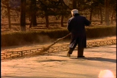China, woman sweeping with primitive broom made of tree branches Stock Footage
