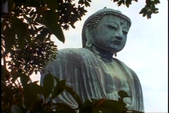 The Kamakura Buddha, close-up framed in tree leaves,  pan right Stock Footage
