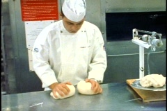 The Queen Elizabeth 2, QE2 galley, baker rolls two large balls of dough Stock Footage