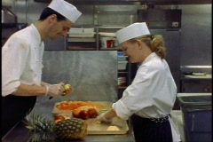 The Queen Elizabeth 2, QE2 galley, two people cutting fruit Stock Footage