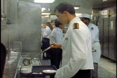 The Queen Elizabeth 2, QE2 galley, waiter ladles soup, medium shot Stock Footage