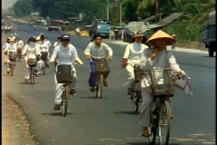 Vietnam, Bicycles on highway, young girls in white gown-like dresses Stock Footage