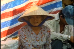 Ho Chi Minh City, Saigon Market, close-up of woman in conical hat Stock Footage