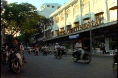 Ho Chi Minh City, Saigon, Continental Hotel, motor scooters passing Stock Footage