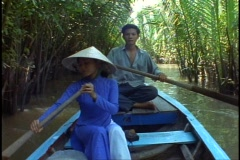 Vietnam jungle, small river, canoe, POV, palms overhang, woman paddles Stock Footage