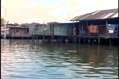 Boat ride through canals (klongs) of Bangkok, pass homes on stilts, POV Stock Footage