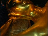 Temple of the Reclining Buddha, The Golden Buddha, close up face of gold, tilt Stock Footage