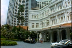 Singapore Raffles Hotel, wide shot, low, tilt up, modern buildings background Stock Footage
