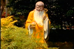 Singapore Tiger Balm Gardens, wise old man in yellow gown, tilt up Stock Footage