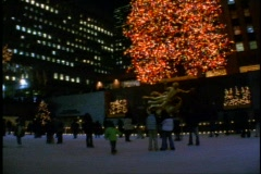 Rockefeller Center at night with the Christmas Tree and skaters on rink Stock Footage