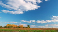 Clouds flying on blue sky over autumn forest and field Stock Footage