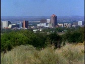 Stock Video Footage of Albuquerque, wide shot overlooking city with sagebrush in foreground