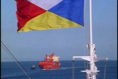 Los Angeles Harbor, freighter moving in, flag in foreground Stock Footage