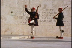 Greek Guards (tights, pom pom shoes, caps) four march, two up stairs Stock Footage