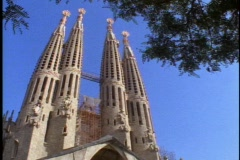 Barcelona, Gaudi, Sagrada Familla Church, 4 towers, pan left,  trees Stock Footage