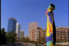 Large Jean Miro public mosaic statue, giant tower,  traffic, pan right Stock Footage