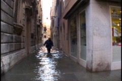Venice woman wading knee deep through the water in a back street Stock Footage