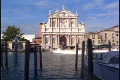 Venice church on the grand canal, still, from shore, boats pass Stock Footage