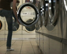 Woman taking off pants at a laundromat Stock Footage