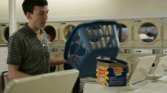 Young man pouring too much detergent at laundromat Stock Footage