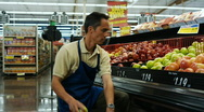 Stock Video Footage of grocery clerk putting apples away