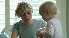 mother watching baby feed herself - stock footage