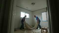 Couple laying down drop cloth to paint a room Stock Footage