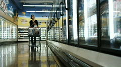 Woman with a baby grocery shopping Stock Footage