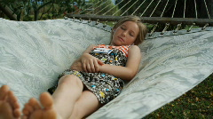 Girl in a hammock listening to an iPod Stock Footage