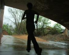 Woman running under an overpass Stock Footage