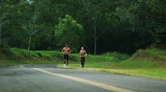 Two people jogging on the side of the road Stock Footage