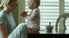 Mother and baby eating breakfast Stock Footage