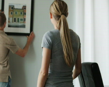 Couple hanging a picture on the wall Stock Footage