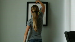 woman deciding which picture to hang on the wall - stock footage