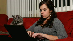 Girl working at computer with gray cat Stock Footage