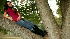 Man sneaking up on Girl sitting on tree branch Stock Footage
