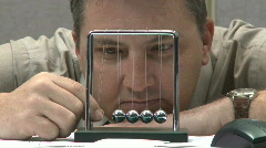 Man looking bored playing with kinetic balls Stock Footage