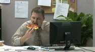 Businessman eating pizza at his desk while working Stock Footage