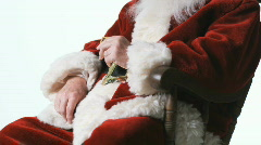 Santa Claus sitting in a rocking chair eating a cookie Stock Footage