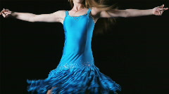 Teenage girl dancing in a blue dress against a black background Stock Footage