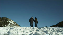 Couple hiking through the snow on snowshoes Stock Footage