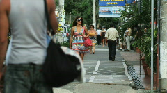 Woman in a dress and sunglasses walking down the street Stock Footage