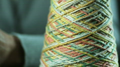 Hands crocheting with multicolored yarn and blue metallic knitting needles Stock Footage