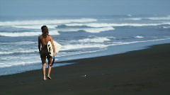 Woman walking down the beach with her surfboard Stock Footage