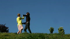 Young couple dancing on a grassy hill Stock Footage
