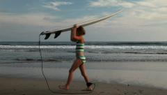 Girl tripping over her surfboard leash while she carries her board Stock Footage