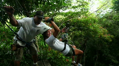 Young woman riding a zipline on a canopy tour - stock footage