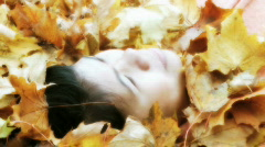 Asian woman laying in a pile of autumn leafs - stock footage